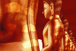 Golden Buddha images sculpture at an ancient temple in Thailand. Abstract striped shadow with sunlight shines on the golden Buddha images. Thai Buddhist sculpture. Selective focus.