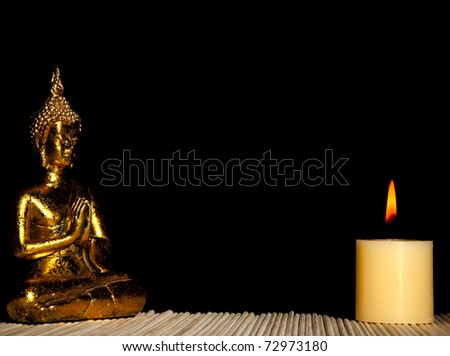 Golden Buddha meditating with candlelight isolated over black