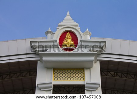 Golden Buddha on the front wall of the roof of the entrance hall. - stock photo