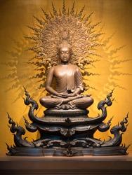 Golden Buddha sculpture in lotus position sitting on an orange background