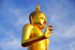 Golden Buddha statue with blue sky background.