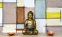 Golden buddha statue with diya lights. Geometric background.