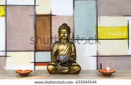 Golden buddha statue with diya lights. Geometric background. #633044144