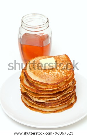 golden buttermilk pancakes and jar of honey isolated on white