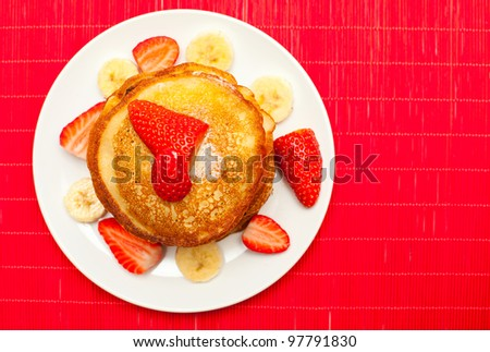 golden buttermilk pancakes with strawberry and banana on red