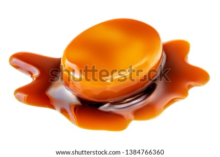 Golden Butterscotch toffee candy caramel with flowing sauce on a top. Sweet treat  isolated on a white background, macro.  #1384766360