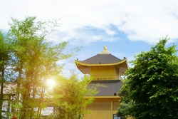 Golden castle is  Japanese architecture building in J-park,Thailand  shape like at  Kinkaku-ji temple,Japan.Gold pavilion around with bamboo tree,sunlight,cloud and blue sky background.