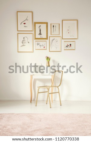 Golden chair by an elegant vanity table with a mirror by a white wall with drawings gallery in a feminine bedroom interior with a pink rug