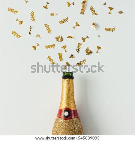 Golden champagne party bottle with confetti on bright background. Flat lay. Celebrate concept. #545039095