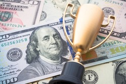 Golden champion trophy award on US dollar bill banknotes background. Successful or achieve business objective target, business management, leadership, first place in business concept.