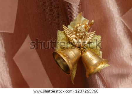 golden cherub figure with two jingle bells. Elegant christmas decoration with Smiling cherub copper colored and two jingle bells on brown background. Cherub for Christmas tree decoration