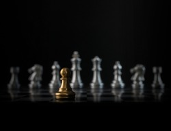 Golden chess pawn is facing the silver opponent chess on black background. Leader, leadership, business strategy, challenge, brave or fearless concept.