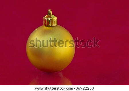Golden christmas ball in red background with some reflection
