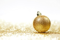 Golden christmas ball on glitter background with white copy space