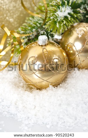 golden christmas ball with christmas tree branch in snow
