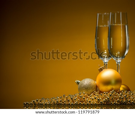 golden Christmas balls and champagne glasses on a gold background