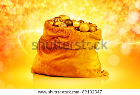 Golden christmas balls and toys in Santa bag on abstract background