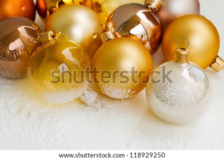 golden christmas balls on  snow white background