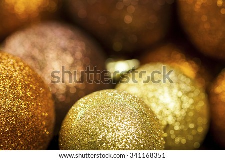 Golden Christmas bauble background with selective focus to a single glitter ball in the foreground with a blurred pile behind giving a warm ambiance and copyspace for your seasonal greeting