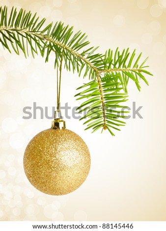 Golden christmas bauble on a string, over bokeh  background