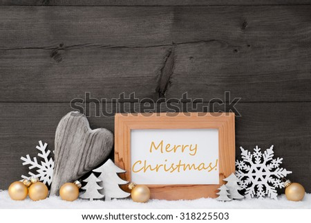 Golden Christmas Decoration On Snow. Heart, Christmas Tree Balls, Snowflake, Christmas Tree.Picture Frame With English Text Merry Christmas.Rustic,Vintage Gray Wooden Background. Black And Withe Image