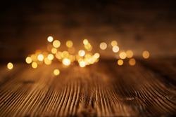 Golden christmas lights on rustic wooden table for a background
