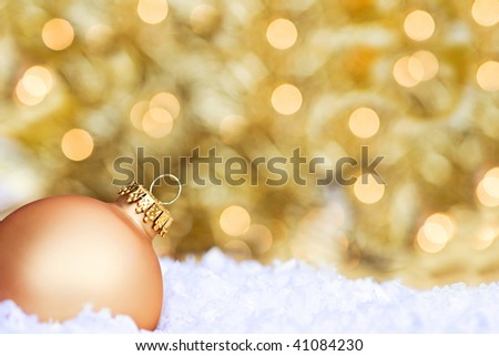 Golden Christmas ornament lying in the snow with bright Christmas lights and room for copy space.