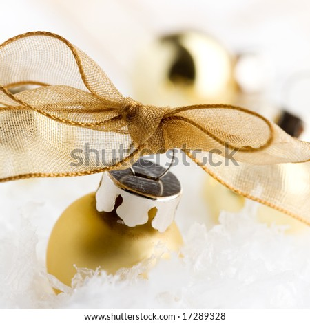 Golden christmas ornaments on white artificial snow