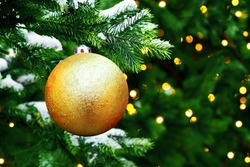 Golden christmas tree ball toy on christmas tree, space for text. Gifts and congratulations holidays concept, xmas, snow