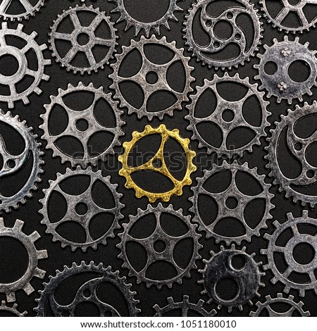 Golden cogwheel in the center, surrounded by metal cogwheels on a black background. Individuality and uniqueness.