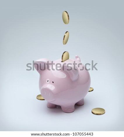 Golden coins falling down into a piggy bank