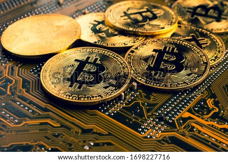 Photo of  Golden coins with bitcoin symbol on a mainboard.