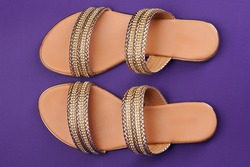 Golden color woman sandals on purple background above top view