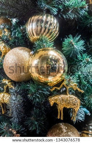 Golden colored Christmas tinsels and baubles hanging from an artificial pine tree. A closeup view. #1343076578