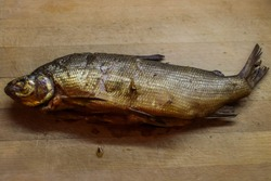 Golden-colored smoked fish whole on a wooden chopping Board