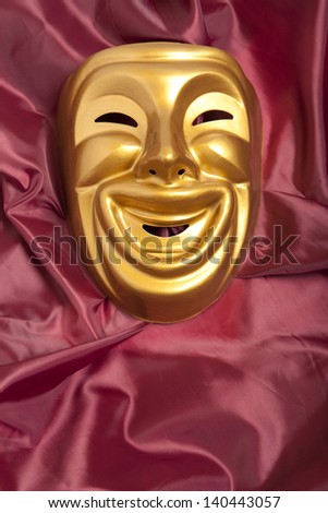 Golden  comedy theatrical mask on satin background