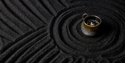 Golden compass on dark stone with dark sand circle background