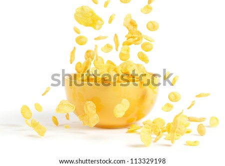 Golden cornflakes falling into the breakfast bowl
