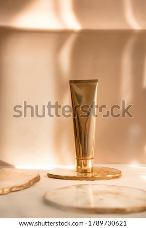 Golden cosmetic tube light pastel color background, lights and shadows. Natural minimalism look, clean concept. Minimal styling, still life. Beauty blogging, branding layout,  skin care ad mock up