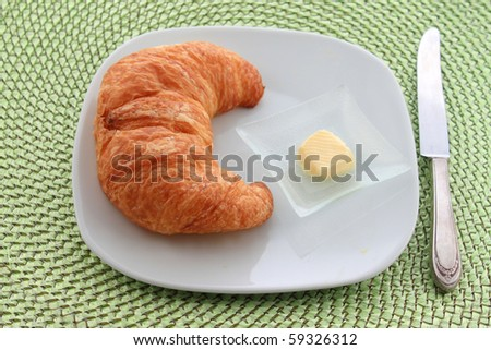 Golden croissant with orange slice on a white plate with a knife and a pat of butter on a green wicker placemat