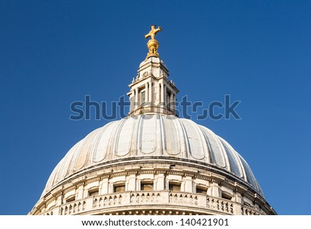 Golden cross on dome of St Pauls Cathedral in London England at dusk as the sun is setting low in sky.