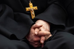 Golden cross with crucifixion of Jesus on the chest of a priest in black clothes. Hands together are blurred out of focus. Shallow depth of field. The symbol of the Orthodox religion.