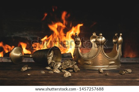 Golden crown and a goblet full of gold on the king table over burning fire background. #1457257688