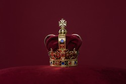 Golden crown on a velvet cushion on a deep red background with copy space