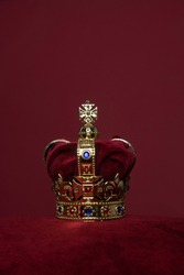 Golden crown on a velvet cushion on a deep red background with copy space in a vertical image