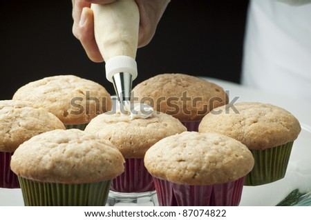 Golden cupcakes with butter cream being piped on by pastry chef/Fresh Baked Cupcakes