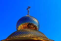 Golden cupola with orthodox cross . Symbol of Christianity . Church dome against blue sky