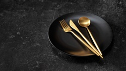 Golden cuttlery placed on black plate on black background