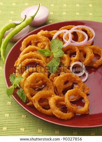 golden deep fried onion rings and vegetables