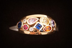Golden diamond ring. Beautiful ring with different color gemstones.